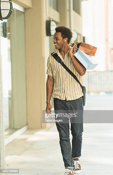 Man walking on street with shopping bags