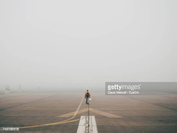Man Walking On Tempelhofer Feld In Fog