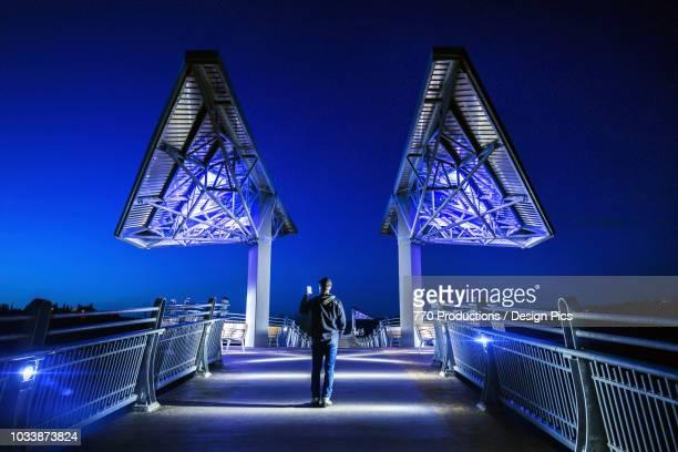 man walking on terwillegar park bridge at dusk - edmonton stock pictures, royalty-free photos & images