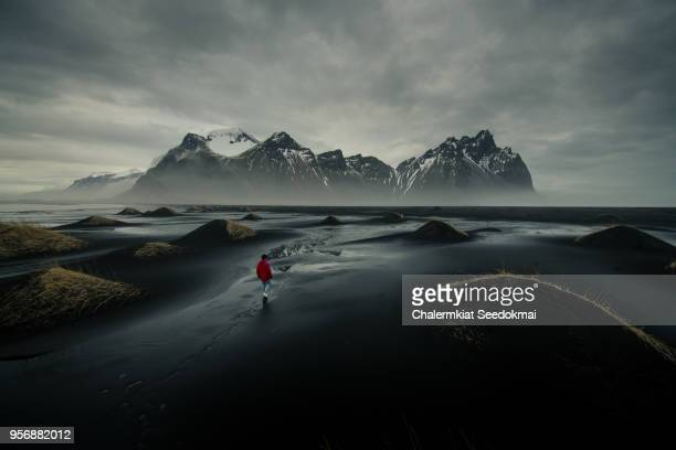 A man walking on the black sand at Vestrahorn, Iceland