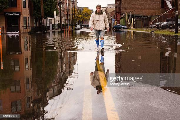 Homem a andar na rua inundada após o furacão de areia landfall