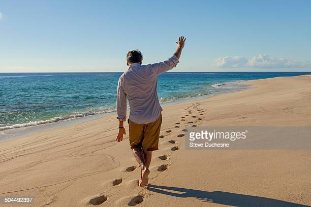 Man walking on the footprint in the sand