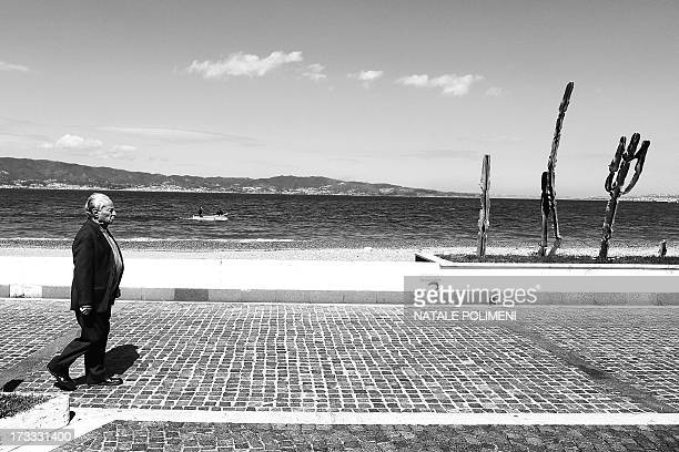 Man walking on the promenade of my city. In the background, a fishing boat in the waters of the Strait of Messina and Sicily.