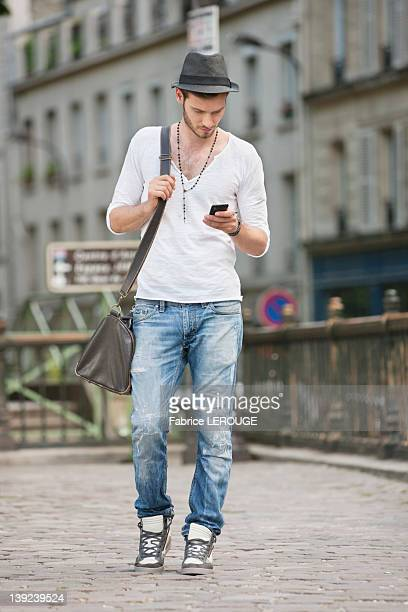 Man walking on the road and text messaging with a mobile phone, Paris, Ile-de-France, France