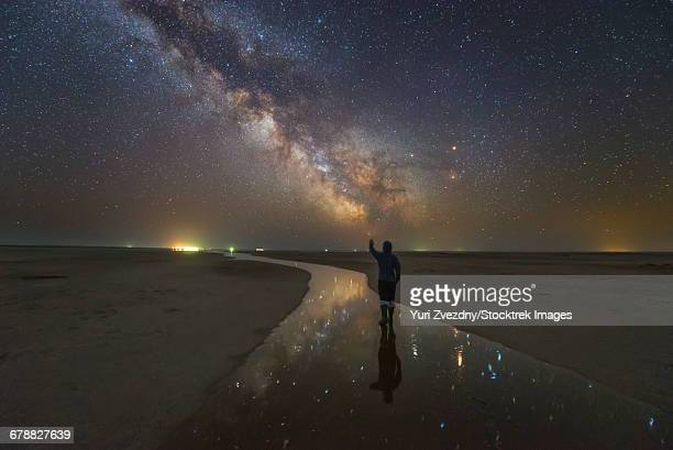 A man walking on the salt river at night under the Milky Way with stars reflected in the river, Russia.
