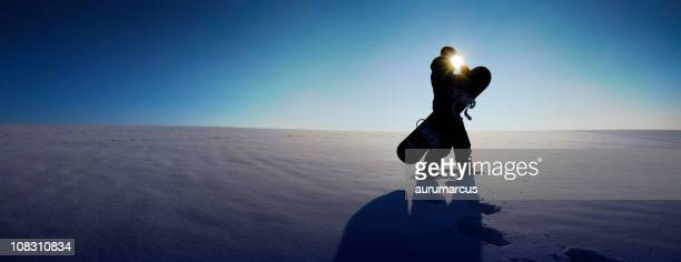 Man walking on the snow with his snowboard