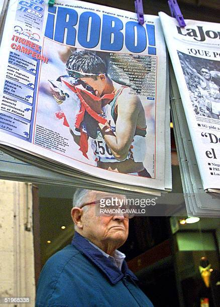 A man walking on the street passes Mexican newspapers showing the photographs of walker Bernardo Segura who was disqualified in the Olympic Games in...