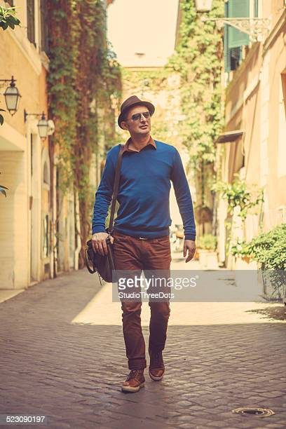 uomo che cammina per strada - solo un uomo maturo foto e immagini stock