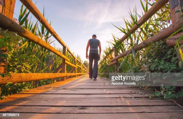 man walking on the wooden bridge