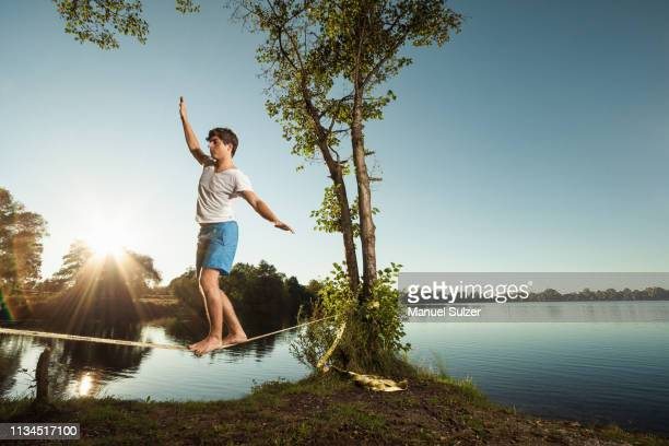 man walking on tight rope outdoors - gleichgewicht stock-fotos und bilder