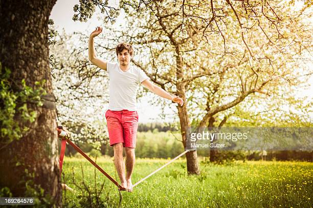 Man walking on tightrope in field