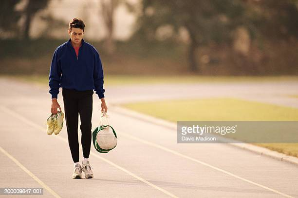 Man walking on track, carrying shoes and duffle bag