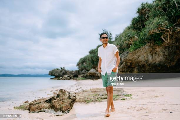 man walking on tropical beach, japan - blue shorts stock pictures, royalty-free photos & images