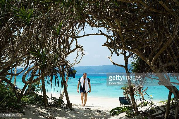 Man walking on tropical beach with Pandanus trees