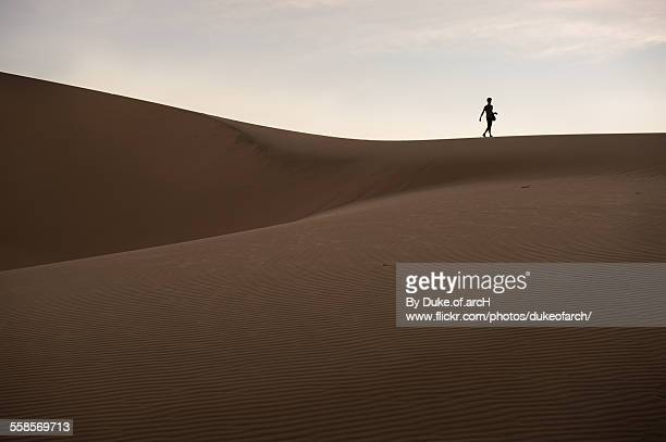a man walking on white sand dune : mui ne - free of charge stock photos and pictures
