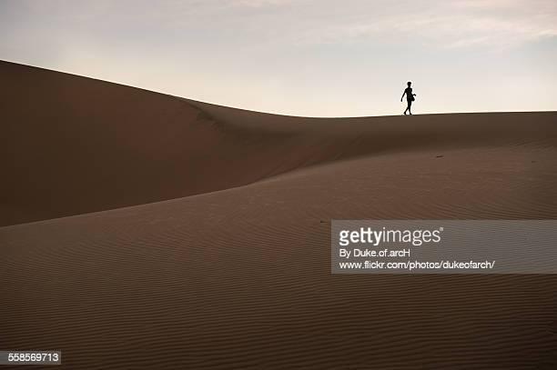 a man walking on white sand dune : mui ne - gratis - fotografias e filmes do acervo