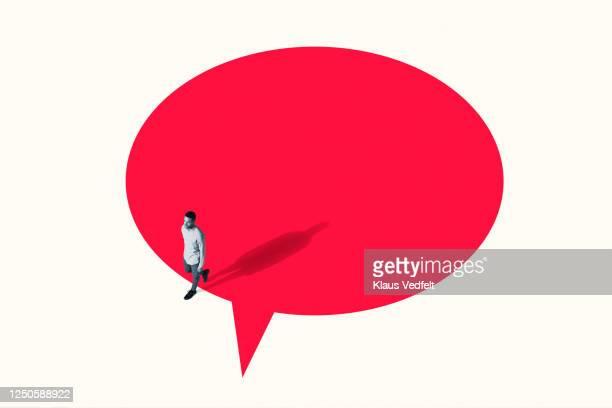man walking out from vibrant red speech bubble - comunicacion fotografías e imágenes de stock