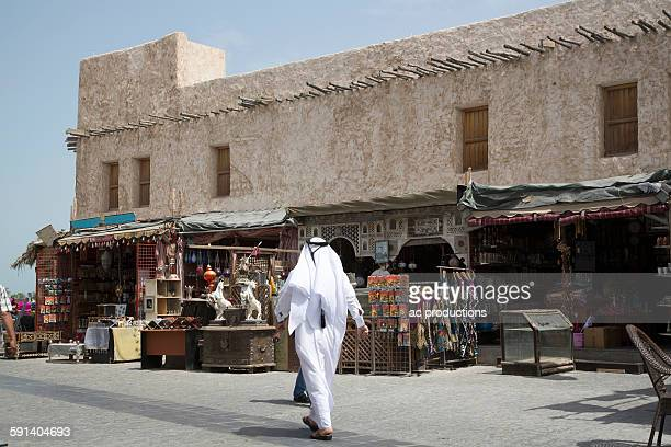 man walking outside market on doha sidewalk, doha, qatar - doha stock pictures, royalty-free photos & images