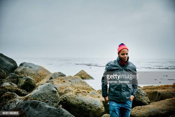Man walking over boulders on beach shoreline