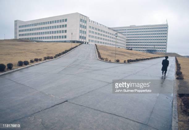 A man walking past a modern building North Korea February 1973