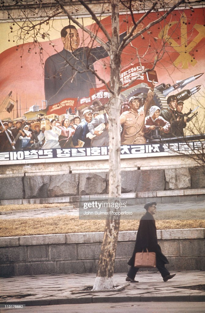 A man walking past a poster depicting Communist leader Kim Il-sung and North Korean revolutionary forces, North Korea, February 1973.