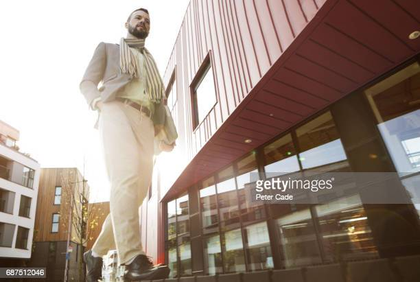 man walking past city buildings - one man only stock pictures, royalty-free photos & images