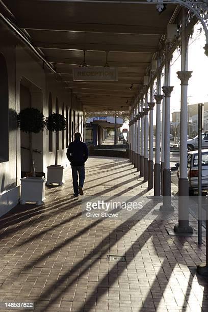 Man walking past Rose Hotel.