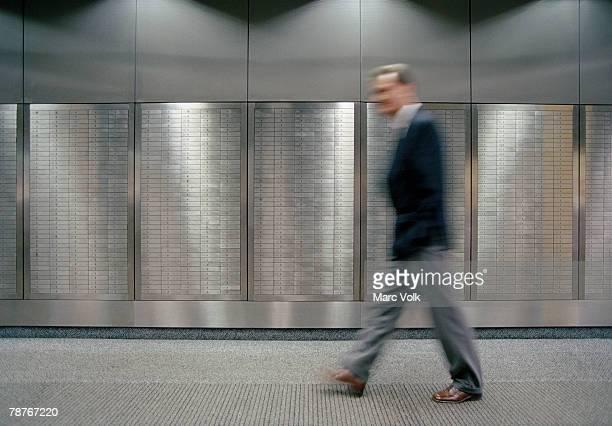 A man walking past safety deposit boxes