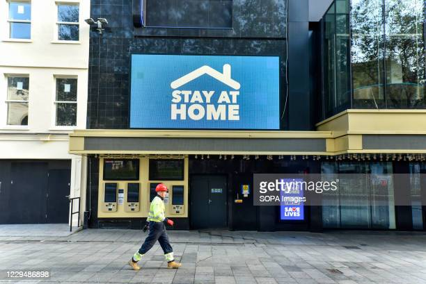 Man walking past the Odeon Luxe in Leicester Square where a digital screen showing a message saying Stay at home'. England has entered into the 2nd...