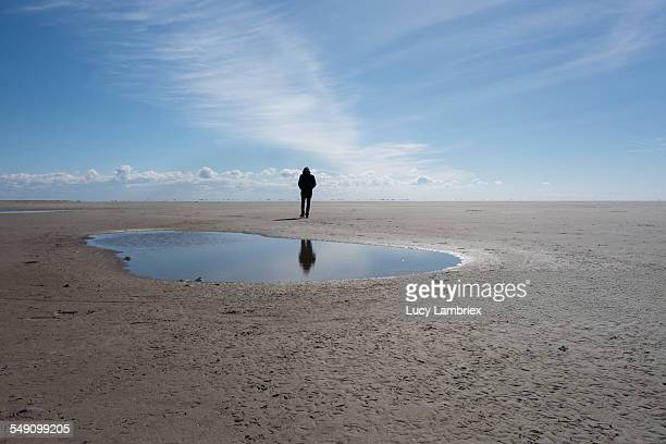 Man walking, reflected in a puddle on a beach