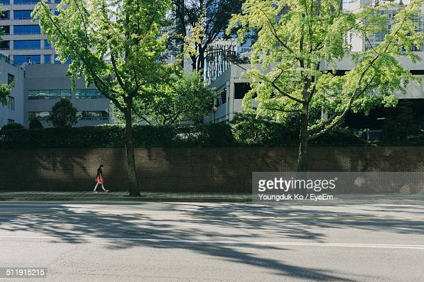 man walking roadside in city - roadside stock pictures, royalty-free photos & images
