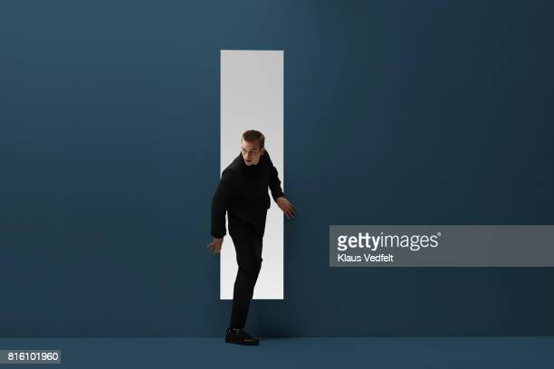 man walking threw rectangular opening in coloured room - peeping holes ストックフォトと画像