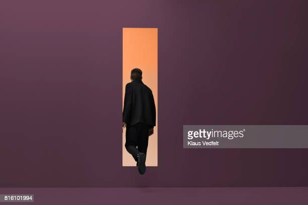 man walking threw rectangular opening in coloured room - schwarz farbe stock-fotos und bilder