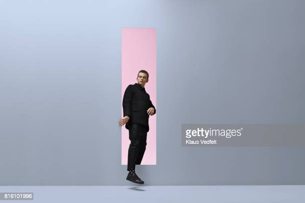 Man walking threw rectangular opening in coloured room