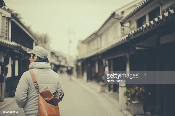 man walking through an old town - präfektur okayama stock-fotos und bilder