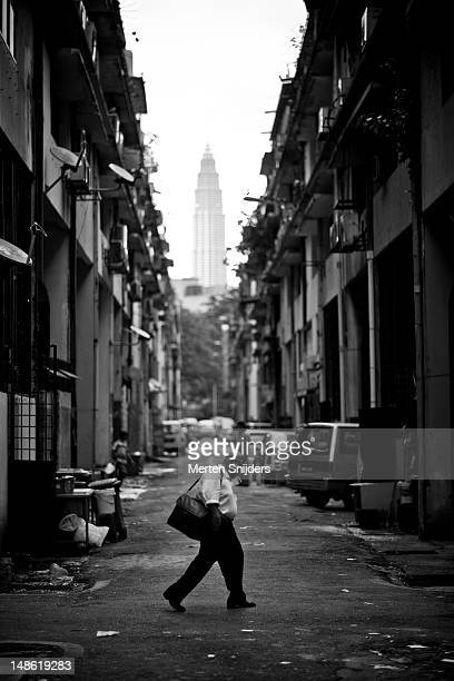 man walking through back alley, with petronas towers in the background. - merten snijders - fotografias e filmes do acervo