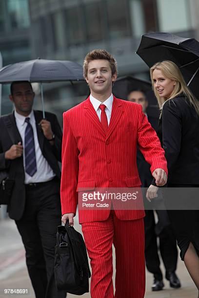 man walking through city in red suit
