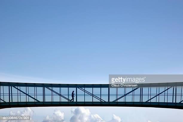 Man walking through covered bridge in sky