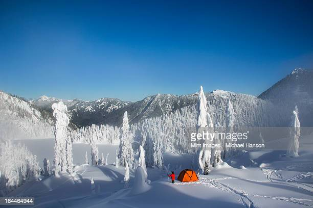 A man walking through deep powder to his campsite in the snow covered Cascade Mountains overlooking Snow Lake.