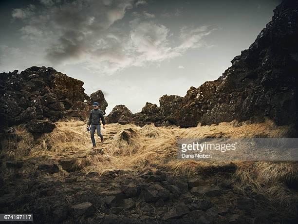 A man walking through grass and rocks.