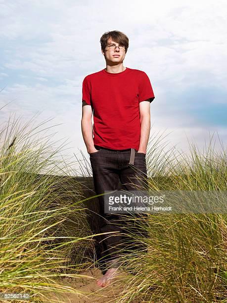 Man walking through grass in sand dune
