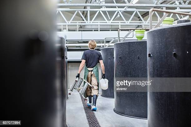 Man walking through hatchery tanks in fish farm