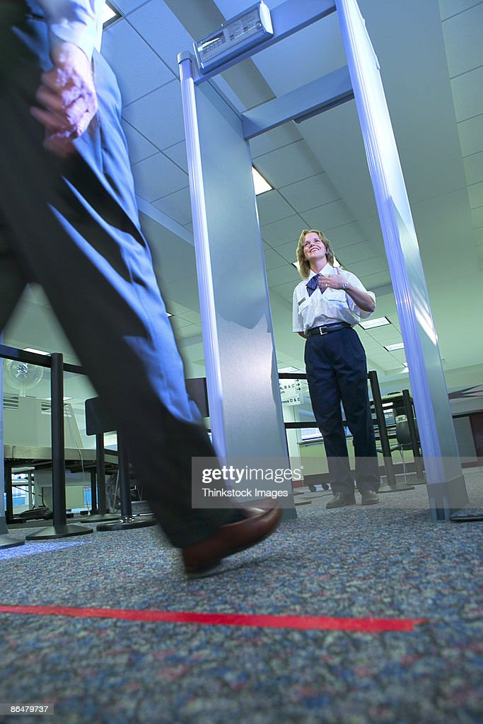 Jew Detector: Man Walking Through Metal Detector At Airport High-Res
