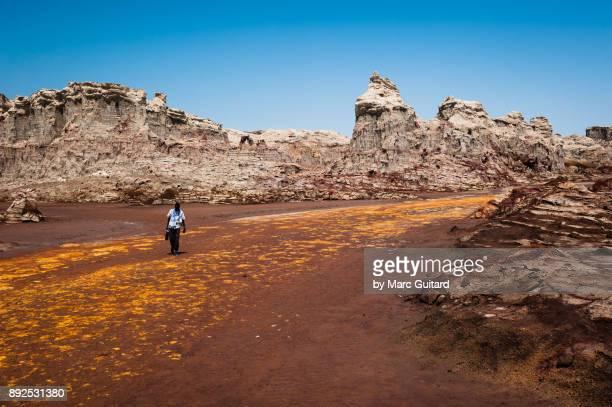 a man walking through mountains of salt near dallol in the danakil depression, ethiopia - danakil depression stock pictures, royalty-free photos & images