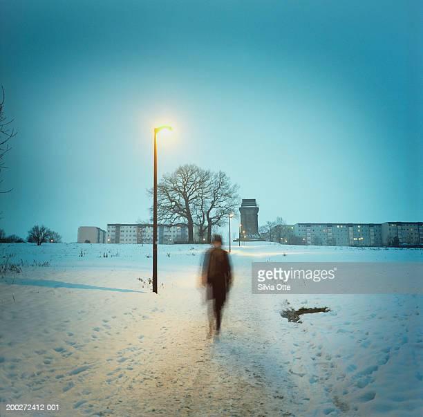 Man walking through path in snow (blurred motion)