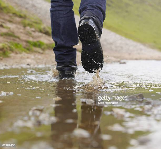 man walking through puddle