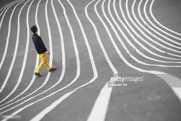 man walking through superkilen park in copenhagen - copenhagen stock pictures, royalty-free photos & images