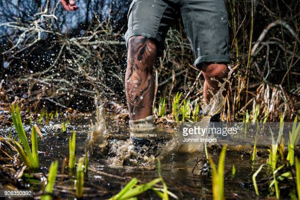 man walking through swamp, low section - dirty feet stock pictures, royalty-free photos & images