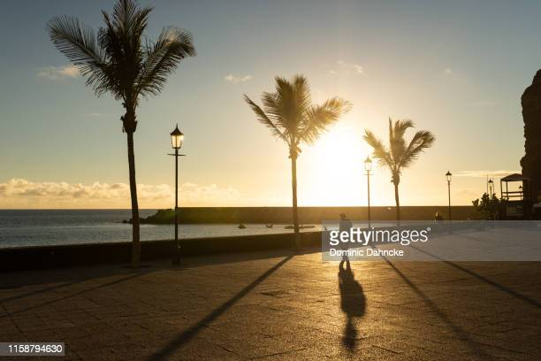 man walking through tazacorte´s promenade at sunset (la palma, canary islands, spain) - atlantic islands stock pictures, royalty-free photos & images