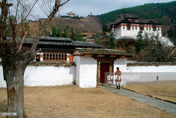 A man walking through the grounds of the Ugyen Pelri Palace in Bhutan The Paro Dzong can be seen on the hill behind